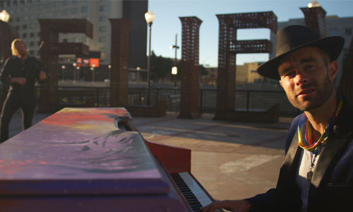 Artist outside playing the piano